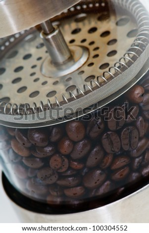 Coffee beans in a french press on white - stock photo