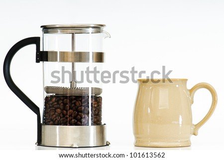Coffee beans in a french press on white with a mug - stock photo