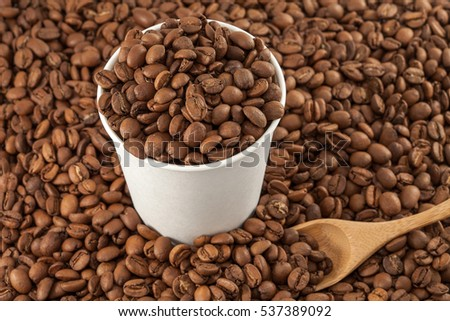 Coffee beans in a paper cup