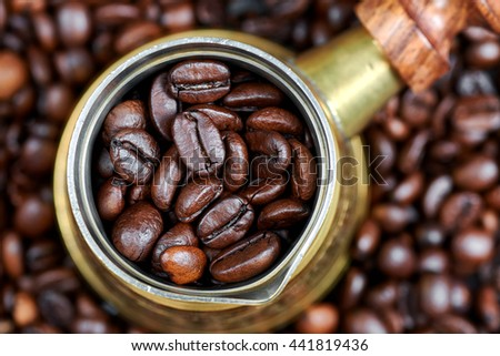 Coffee beans in a turkish coffee pot - stock photo