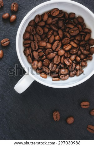 Coffee beans in a white cup - stock photo