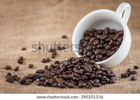 Coffee beans in a white cup over sack texture and background