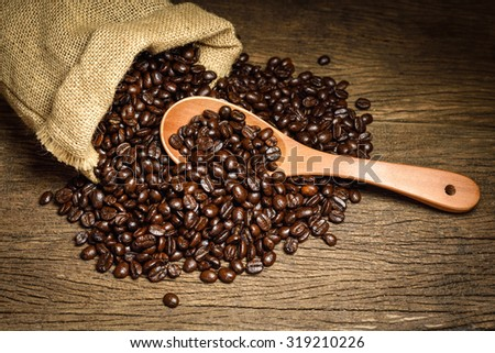 Coffee beans in a wooden scoop and spilling out from a hessian bag on old wooden