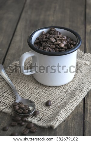 Coffee beans in an enamel mug on the wooden background