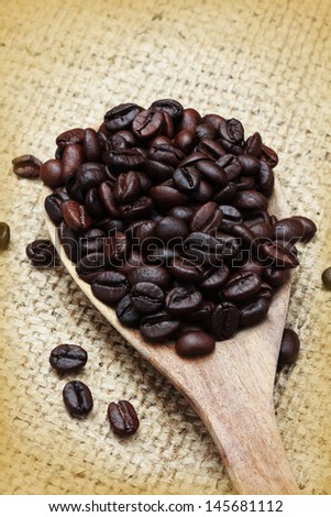 Coffee beans in an old wooden scoop - stock photo