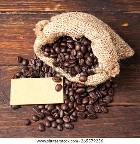 Coffee beans in bag and paper note for text on wooden table