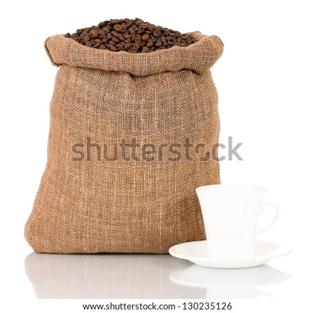 Coffee beans in burlap sack and cup with saucer, isolated on white background