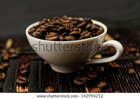 Coffee beans in ceramic white coffee cup