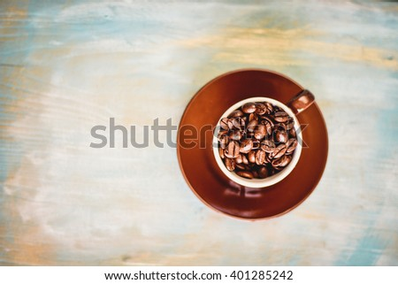 Coffee beans in coffee cup  on blue background. - stock photo