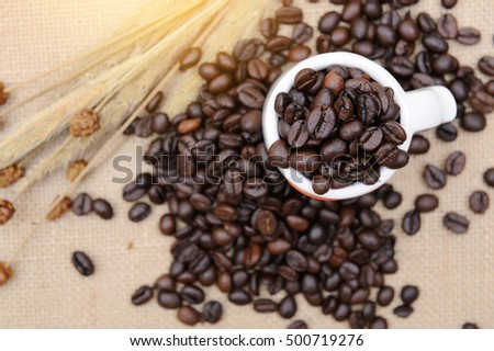 Coffee beans in coffee cup on sack , Top view