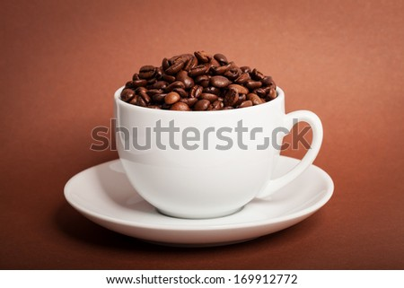 Coffee beans in cup on brown background - stock photo
