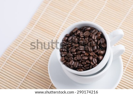 Coffee beans in cup on wood background