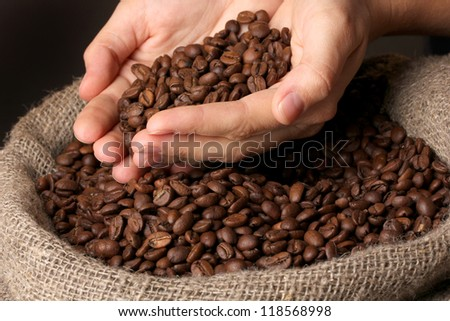 Coffee beans in hands on dark background