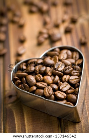 coffee beans in heart form on wooden table