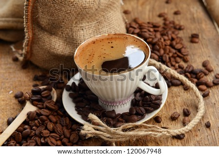 coffee beans in jute sack behind  cup of black coffee