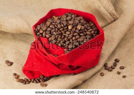 Coffee beans in red velvet sac - stock photo