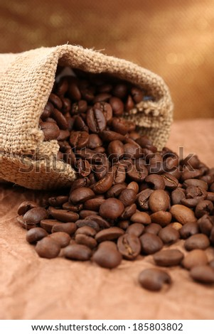 Coffee beans in sack on table close-up - stock photo