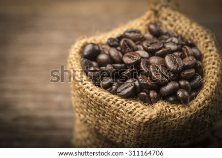 Coffee beans in sack on wood table - stock photo