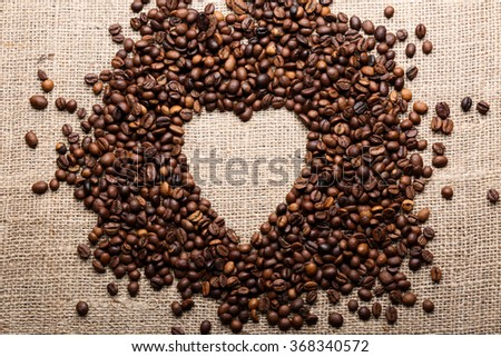Coffee beans in shape of heart on burlap background - stock photo