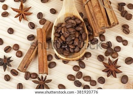 Coffee beans in spoon, cinnamon and stars of anise on a wooden background - stock photo