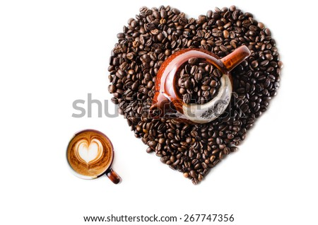 Coffee beans in the shape of a big heart with kettle & mug  - stock photo