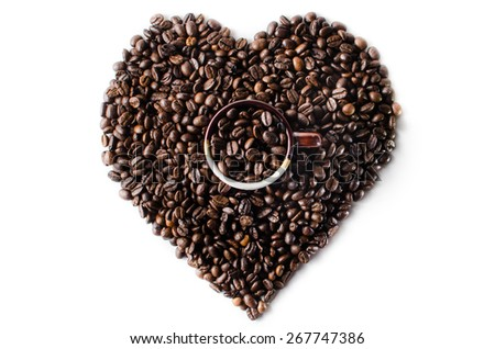 Coffee beans in the shape of a big heart with mug - stock photo