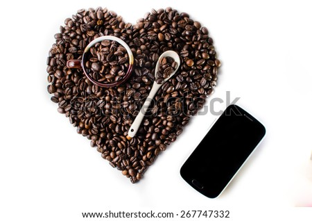 Coffee beans in the shape of a big heart with mug ,spoon & mobile - stock photo