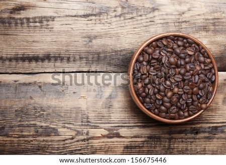 Coffee beans in wooden bowl on wooden background.  - stock photo