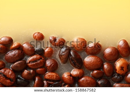 Coffee beans in yellow wax as background with space for text