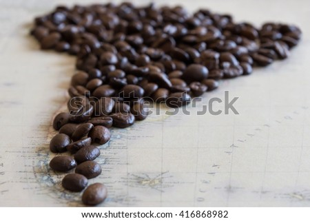 Coffee beans laid out on a generic map of south america.