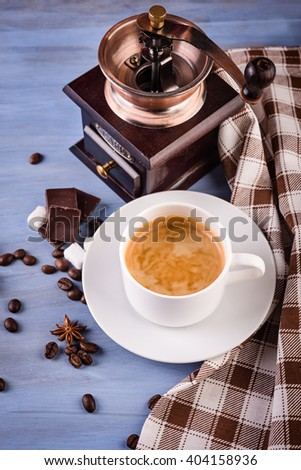 coffee beans, mill and coffee cup on blue table - stock photo