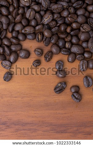 Coffee beans mixed medium and dark roasted on wooden background with copy space, food background