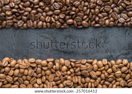 Coffee beans of arabica and robusta  on black wooden background with blank space. - stock photo