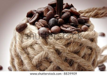 Coffee beans on burlap rope - stock photo
