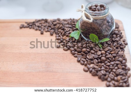 Coffee beans on the wooden background with green leaves - stock photo