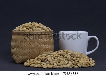 Coffee beans on wicker  Basket and coffee mugs. - stock photo