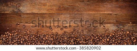 coffee  beans on wide rustic oak background - stock photo