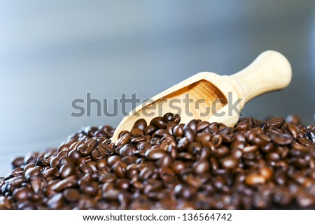 Coffee beans on wooden spoon. - stock photo