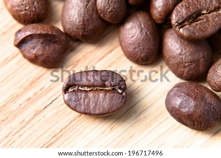 coffee beans on wooden table , focus on foreground - stock photo