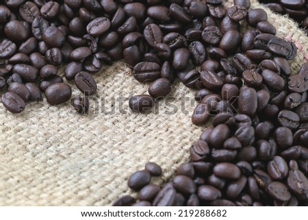 Coffee beans placed on bag sack for foods background. - stock photo