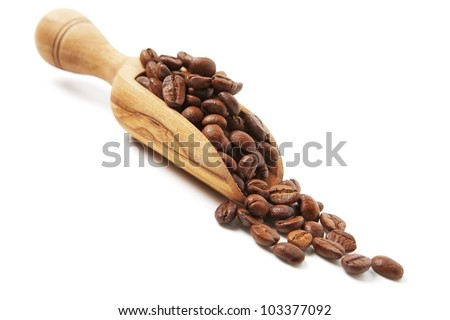Coffee beans poured from wooden scoop - stock photo