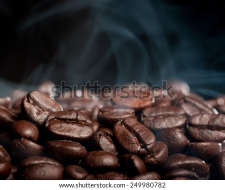 Coffee beans roasting with smoke - stock photo