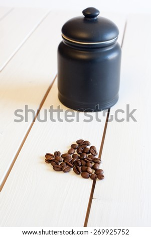 coffee beans shaped as a heart in front of a black jar of china from above - stock photo