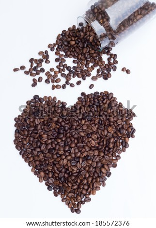 Coffee beans spilled from a glass bottle - stock photo