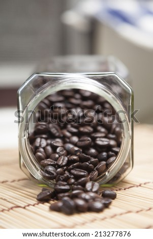 Coffee beans spilled from glass bottle on a wooden table top. - stock photo