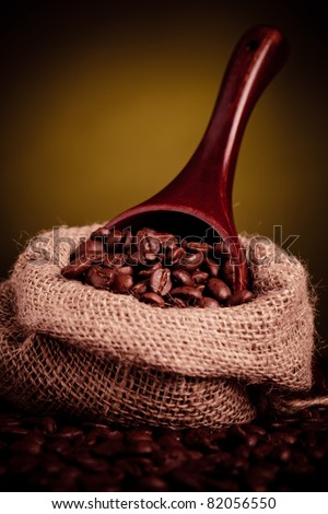 coffee beans spilling out of wooden scoop with copy space - stock photo