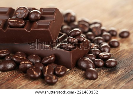 Coffee beans with chocolate glaze and dark chocolate on wooden background - stock photo