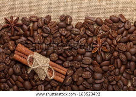Coffee beans with cinnamon sticks and anise stars on sack cloth background