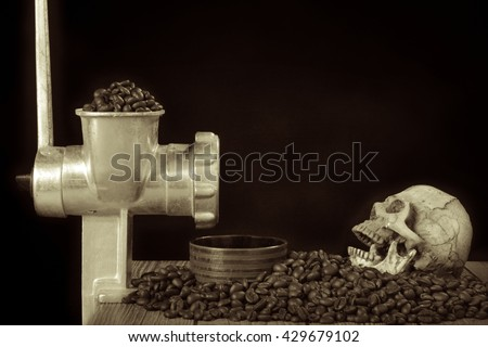 coffee beans with coffee grinder and a skull , still life style