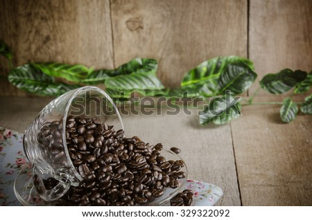 coffee beans with  cup and Floral tablecloth on wood table